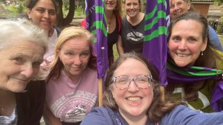 A picture containing 8 women gathered together for a large selfie style photo. There are two purple and green unison flags in the middle of the group